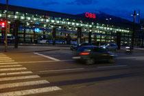 Südtiroler Platz in Innsbruck in den Abendstunden mit Straßenbahn-/Bussteigen der Innsbrucker Verkehrsbetriebe, dahinter der Hauptbahnhof und die Umrisse vom Patscherkofel. Digitalphoto; © Johann G. Mairhofer 2016.  Inv.-Nr. 2DSC04799