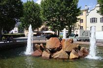 Springbrunnen am Unteren Stadtplatz auf der Freifläche zwischen Stadtgraben, Landesstraße B171 und südwestliche Häuserzeile von Hall in Tirol (im Bildhintergrund). Digitalphoto. © Johann G. Mairhofer 2013.  Inv.-Nr. 1DSC07325