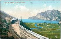 Lokalbahngarnitur der Mori-Arco-Riva-Bahn (1891-1936) auf der Fahrt nach der Endstation Riva (del Garda) und die Mündung der Sarca in den Gardasee. Photochromdruck 9 x 14 cm; Impressum: Joh(ann). F(ilibert). Amonn, Bozen um 1910.  Inv.-Nr.  vu914pcd00070