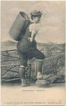 """""""Unterinntaler Sennerin"""" in Arbeitskleidung (Holzknospen, Melkerhose, Strohhut) mit weidengebundener Milchkraxe vor gemalter Hintergrundkulisse (Souvenirbild). Lichtdruck 9 x 14 cm; Impressum. Jos(ef). Herold, Kitzbühel 1907.  Inv.-Nr vu914ld00310"""