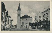 """Gasthof """"zur Alten Post"""", Pfarrkirche St. Laurentius und Gasthof """"zur Neuen Post"""" (v.l.n.r.) am Kirchplatz (heute: Andreas-Hofer-Platz) in Wörgl, Bzk. Kufstein, Tirol. Lichtdruck 9 x 14 cm; Impressum: Rud(olf). Berger, Wörgl um 1920. Inv.-Nr. vu914ld00332"""