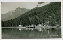 Bootshaus In Pfahlbauweise und Wassersprungturm aufgeständert im Reintalersee, Gemeinde Kramsach, Bezirk Kufstein, Tirol. Gelatinesilberabzug 9 x 14 cm; Impressum: Ad(olf). Künz, Innsbruck, Anichstraße 32, um 1930.  Inv.-Nr. vu914gs00735