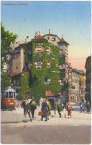 """Straßenbahntriebwagen der Linie 2 von der Haltestelle """"Innbrücke"""" kommend (links – nicht im Bild) beim Gasthof OTTOBURG am Eingang zur Altstadt. Photochromdruck 9x4cm; K(arl). Redlich, Innsbruck um 1910.  Inv.-Nr. vu914pcd00189"""