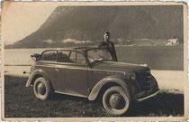 """Junger Mann mit einem Opel Olympia der Bauart Cabriolimousine am Achensee, Bezirk Schwaz, Tirol, bez.: """"Zur Erinnerung an meinen Urlaub im Juli 1939."""" Gelatinesilberabzug 9 x 14 cm (Amateuraufnahme). Inv.-Nr. vu914gs00014"""