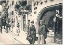 Dame und Herr in Wetterschutzkleidung für Motorradfahrer bei einem Aufenthalt in der Altstadt von Kitzbühel in Tirol vor dem Café Praxmair, Vorderstadt 17. Gelatinesilberabzug 7,5 x 11,0 cm, Amateuraufnahme um 1965.  Inv.-Nr. vu7511gs00003