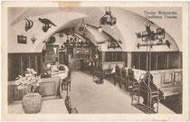 """Jagdtrophäen in der """"Tiroler Weinstube"""" vom Gasthof (heute Hotel) """"Traube"""" in der Bezirkshauptstadt Lienz (Osttirol), Hauptplatz 41. Lichtdruck 9 x 14 cm; Impressum: Hans Fracaro, Lienz 1924.  Inv.-Nr. vu914ld00316"""