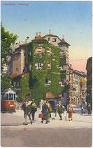 """Straßenbahntriebwagen der Linie 2 von der Haltestelle """"Innbrücke"""" kommend (links – nicht im Bild) beim Gasthof """"Ottoburg"""" am Eingang zur Altstadt. Photochromdruck 9 x 4 cm; K(arl). Redlich, Innsbruck um 1910.  Inv.-Nr. vu914pcd00189"""