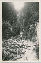 Holzbringung mittels Trift (wilde Flößerei) auf der Brandenberger Ache von der Erzherzog-Johann-Klause oder Steinbergklause aus bis zur Kramsacher Lände. Gelatinesilberabzug 9 x 14 cm ohne Impressum um 1940.  Inv.-Nr. vu914gs01176