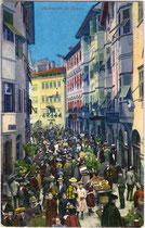 Buntes Markttreiben am Obstplatz in der Altstadt von Bozen, Südtirol. Photochromdruck 9 x 14 cm; Impressum: Joh(ann). F(ilibert). Amonn, Bozen 1915.  Inv.-Nr. vu914pcd00093
