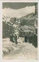 Nordabschnitt der Maria-Theresien-Straße mit der Annasäule in Innsbruck gegen die Nordkettte nach ergiebigen Schneefällen. Gelatinesilberabzug 9 x 14 cm ohne Impressum, um 1940.  Inv.-Nr. vu914gs00662