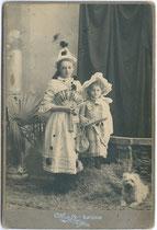 Kufsteiner Kinder im Faschingskostüm. Gelatinesilberabzug auf Untersatzkarton mit Rückseitenaufdruck im Jugendstil 16,6 cm x 10,8 cm (Cabinet-Format); Aufnahme: A(nton). Karg, Kufstein um 1907.  Inv.-Nr. vuCAB-00041