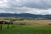 Ein Blick vom Wanderweg am Waldrand des Ith mit Blick auf den östlichen Teil Eschershausens und den Ortsteil Wickensen. Im Hintergrund der Stadtberg / Homburgwald.