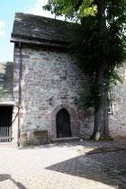 Der Eingang zur Kapelle, links die Galgensteine, rechts die eine verbliebene Linde, heute ein Naturdenkmal.