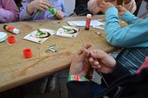 Kleine Kunstwerke aus Papier, die aufgefädelt eine Kette oder ein Armband ergeben