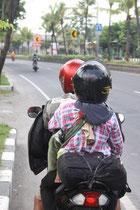 Eine kleine Familie auf einem Roller (zwischen den beiden ist ein kleines Baby. hab ich leider nicht auf das Bild bekommen..)