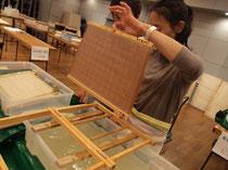 ワークショップ風景。半紙(約B4サイズ)を漉いたあと、紙床(かんだ)に伏せるための説明