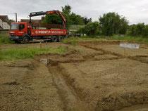 Arrivée des premiers matériaux ( 4 palettes de ciment et 45 tonnes de gravier tout venant béton 0-31,5 ) pour couler les 22 m3 de fondations, de 60 cms de large sur 35 cms de profondeur, sur 64 mètres linéaire.