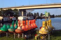 Am Hafenbecken lagern Bojen und anderes Sicherungsmaterial des Wasser- und Schifffahrtsamtes.