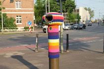 """Juni 2012 - Zum Kulturhauptstadtjahr 2010 wurden in Ruhrort mehrere Videostelen aufgestellt, in denen alte Ansichten von Ruhrort zu sehen sind. Eine """"Strickguerilla"""" hat die nackte Stele am Vinckeplatz nun mit einem bunten Wollumhang verkleidet."""