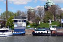 An der Rheinbrücke (im Hintergrund die Brückentürme) steht das Haus des Hafenmeisters mit dem Pegel