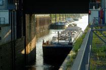 Vom Hafenkanal fährt ein zweites Schiff in die Schleusenkammer.