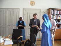 Der Oberbürgermeister von Würzburg, Herr Rosendahl übergibt den Schwestern ein Geschenk.