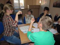 Projektmitarbeiterin Anna Brönner zeigt den Kindern, wie es geht