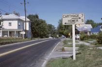 Eines dieser typischen, kuriosen Autofahrererlebnisse in den USA: Wir befinden uns in Ohio, 7 Meilen von Karthago entfernt (nach links) und 5 Meilen von Homer entfernt (nach rechts). Man beachte, dass üblicherweise keines der Grundstücke eingezäunt ist.
