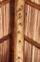 Eine Reihe von Fledermäusen, kopfunter am Dachgiebel.