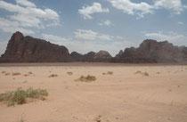 """Wind und Wetter schliffen über jahrtausende den rötlichen Sandstein des Wadi Rum zu bizarren Formen (im Hintergrund """"die sieben Säulen der Weisheit""""). Dass es in der Tat stürmisch zugehen kann, erlebten auch wir, als starke Winde den Sand aufwirbelten."""