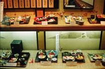 Vitrine vor dem Shushi-Restaurant: Alle Speisen sind aus Plastik. Der Gast kann so dem Bedienungspersonal draussen vor dem Lokal zeigen, was er zu essen wünscht, auch wenn er Japanisch weder sprechen noch (auf der Speisekarte) lesen kann.