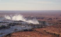 """Die einheimischen Kololo nennen den Victoria-Wasserfall Mosi-oa-Tunya = """"Donnernder Rauch"""". Wenn der Zambezi sich auf einer Breite von 1708 m über 110 m in die Tiefe stürzt, ist der Sprühnebel, der bis zu 300 m aufsteigt noch in 30 km Entfernung zu sehen."""