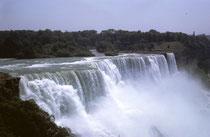 An der Grenze zwischen dem US-amerikanischen Bundesstaat New York und der kanadischen Provinz Ontario, stürzen die Wassermassen des Niagara River in die Tiefe. Im Vordergrund die American Falls (Kantenlänge von 260 m und Fallhöhe von 21 bis 34 m).