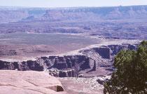 """Aussicht auf den White Rim, eine Sandsteinabbruchkante rund 360 Meter unterhalb des Plateaus, und auf die Flussläufe, weitere 300 m unterhalb des White Rims. Die weitläufige grüne Hochebene dürfte das """"Island in the Sky"""" sein."""