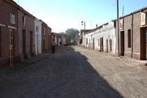 San Pedro de Atacama, Caracotes. Morgens sieht diese Hauptstrasse von San Pedro de Atacama menschenleer und verlassen aus. Am Abend verwandeln sich die Häuser in Bars, Restaurants, Geschäfte usw. und die Strasse ist voller Leben.