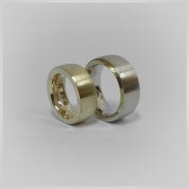 Zwei verschiedenfarbige Ringe in Weiß- und Gelbgold. An den Seiten sind jeweils drei Nieten, aus dem Material des anderen Ringes, angebracht. Unter diesen Nieten befinden sich symbolische Liebesgaben.