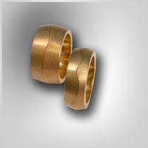 Ringe in Gold. Der Ringkörper hat zur Mitte hin unterschiedlich hohe Steigungen. Diese treffen sich dann in einem welligem, poliertem Grat.