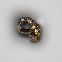 Ringe in Gelbgold. Ein reliefartiges Muster aus verschieden großen Dreiecken durchbricht die polierte, gerundete Außenseite.