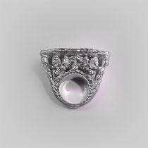 Großer, figuraler Ring in Silber. Vier Engel tragen eine aus floralen Ornamenten bestehende Wölbung.
