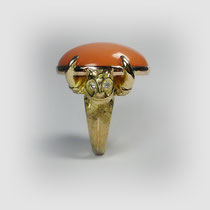 Ring in Gold, stilisierte Eulenköpfe tragen einen großen Cabouchon aus Engelshaut-Koralle. Mit Diamanten.