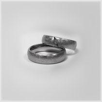 Ringe in Weißgold in klassischer Formgebung mit schraffierter Textur. Im kleineren Ring fasst eine diagonal verlaufende, v-förmige Vertiefung einen Brillianten.