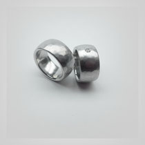 Ringe in Weißgold. Eine weiche Hammerschlagstruktur überzieht die Oberfläche, im kleineren Ring ist ein Diamant gefasst.