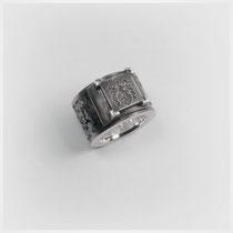 Kräftig strukturierter Bandring in Silber mit gefasstem Wappentableau.
