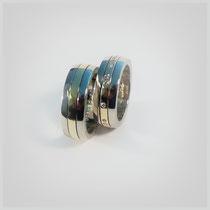 Ringe in zweifarbigen Gold. Ein Gelbgoldband ist ringsherum in der Mitte eingelassen. Im kleineren Ring sind Diamanten, angelehnt an ein Morsezeichen, eingefasst.