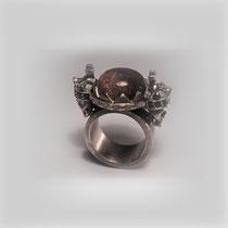 Figuraler Ring in Silber. Zwei gekrönte Totenköpfe fassen einen funkelnden Sonnenstein, mit Onyx.