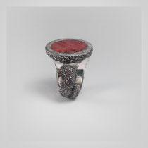 Ring in dunklem Silber, das sich öffnende Füllhorn umschließt einen kreisförmigen Rubin.