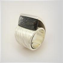 Ring in Silber. Die geöffnete Wicklung fasst einen Quarz mit Turmalinnadeln.