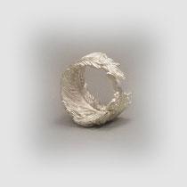 Der Ring in Silber gleicht einer gebogenen Feder.