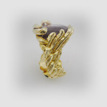 Opulent wirkender Ring in Gold. Federartig gestaltete Gefüge halten einen großen facettierten Rubin.