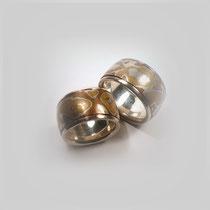 Ringe in Silber, Kupfer und Messing. Ein dreifarbiger Mokume-Gane-Streifen ist in Silber eingefasst.